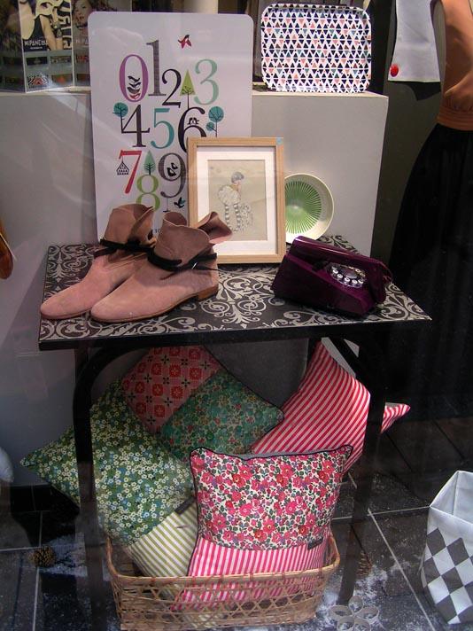 coussins, cadre, bottes dans la vitrine d'un magasin de décoration